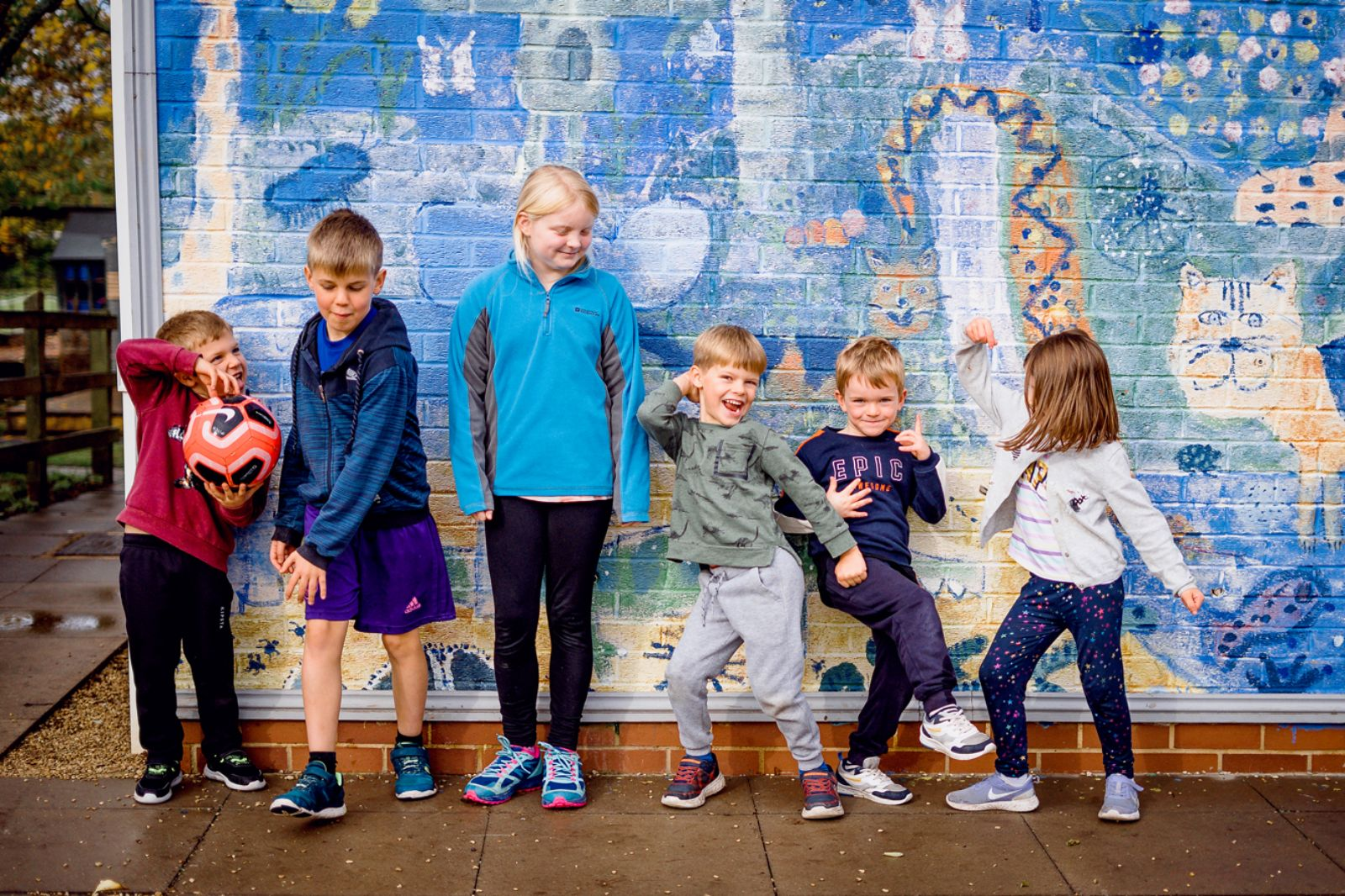 children smiling in front of a wall